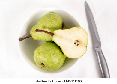Two green pear in  in a white bowl with half a pear slices and stainless steel knife on isolated on white background. Abate fetel pear. Top view