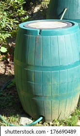 Two green plastic rain barrels are connected to capture and store more rain water. When one barrel is full, surplus will flow into the second.