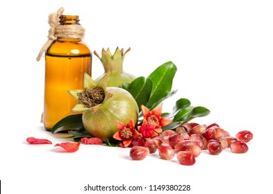 two green pomegranates, bottle with oil and leaves with petals on white background