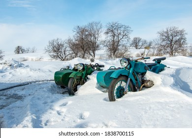 Two green Soviet retro motorcycles parked next to a snowdrift after a snowfall, Kazakhstan, March 2020