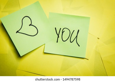 Two green sticky notes with word you and heart symbol on yellow notes