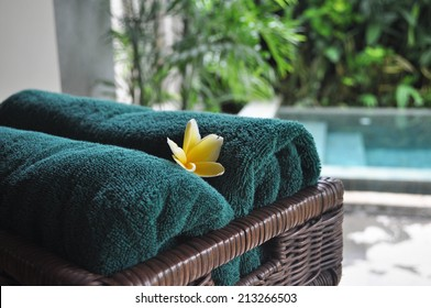 Two green towels with yellow frangipani flower in a wooden basket with a private pool in the resort as the background