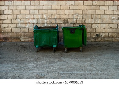 Two Green Trash Dumpsters In Front Of White Brick Wall Front View With Room For Text.