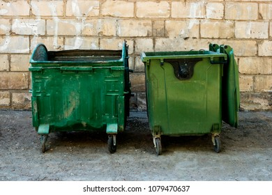 Two Green Trash Dumpsters In Front Of White Brick Wall