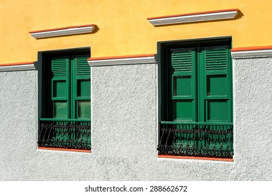Two green windows with wooden shutters on multicolored wall. Canary Islands ,Tenerife. Spain.