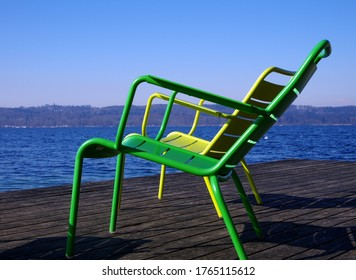 Two green and yellow chairs on a lakeside terrace in the sun