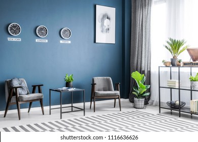 Two grey armchairs, metal rack with decor, window with drapes and plants placed in dark living room interior