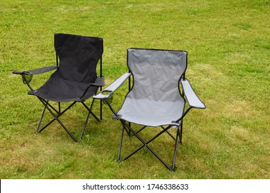 Two grey and black empty folding camping chairs in green lawn grass outdoors in sunny summer day. Camping equipment.