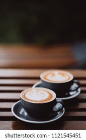 Two grey cups of cappuccino with latte art on wooden table.