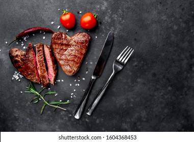 two grilled beef steaks in the form of a heart with spices for Valentine's day on a stone background with copy space for your text. dinner concept for two for Valentine's Day celebration