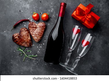 two grilled beef steaks in the form of a heart with spices, a gift with a red ribbon and a bottle of champagne or wine with two glasses for dinner for Valentine's day on a stone background