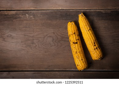 Two Grilled corn cobs on the brown rustic background with copy space. Usually served with the BBQ Butter or Herb Butter