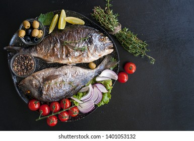 Two grilled Dorado fish with onions, olives, tomatoes and thyme on a black table. The view from the top. Copy space.