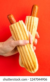 Two grilled french hot dogs in woman's hand on bright background. Junk or fast food. Copy space