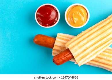 Two grilled french hot dogs with mustard and ketchup on bright background. Junk or fast food. Copy space