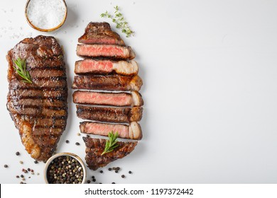Two grilled marbled beef steaks striploin with spices isolated on white background, top view with copy space
