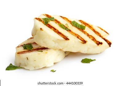 Two grilled slices of halloumi cheese isolated on white in perspective. With grill marks and mint.