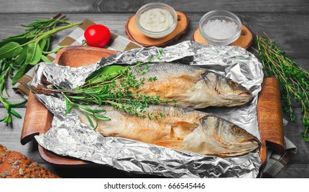 Two grilled whole fish trout on an aluminum foil on a gray wooden background. Additional ingredients for grilled fish greens rosemary, thyme, sage, red pepper, bread, fish sauce tartar.