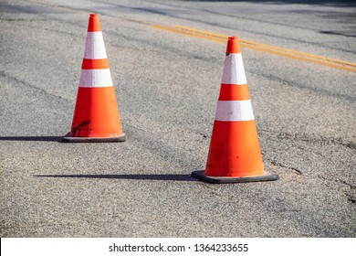 Two grungy orange traffic cones with reflective tape and sharp shadows on cracked asphalt pavement with double yellow line - close-up and selective focus