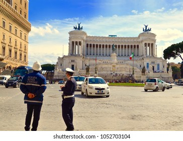 Two Guardia or Italian police officers directing traffic in Rome city centre beside the Victtoriano monument also known as the Wedding Cake. Rome city, Italy, Europe. March  2018