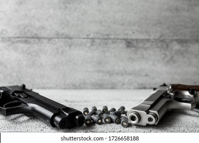two guns with bullets on the gray background