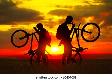 Two guys with bikes on sunset