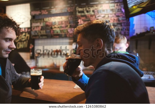 two guys friends sitting in the pub with glasses of dark beer, have fun talking, laughing, clinking glasses and drinking