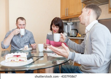 Two guys and   girl at   kitchen table with cake and tea.