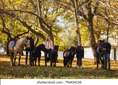 Two guys, girl and a little girl stand with adult horses and ponies in an autumn park.
