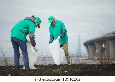 Two guys in greenpeace uniform picking up litter into big sacks while workin outdoors