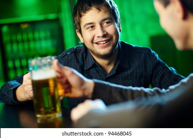 Two guys hanging out in bar with mugs of beer