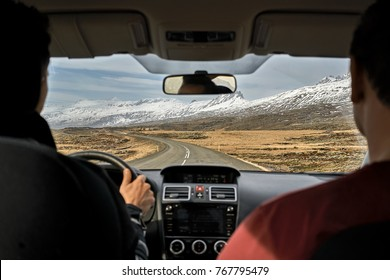 Two guys inside the car driving on the country roadway between fields with brown grass and snowy mountains on the cloudy sky background in Iceland. Sun is shining. Shoot from the back. Horizontal.