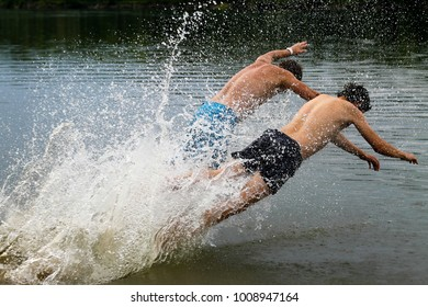 Two guys jump into the water. A lot of spray