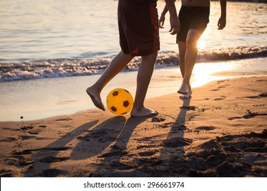 Two guys playing football on the beach at sunset legs closeup