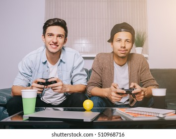 Two guys playing on the console sitting on the couch. European and African friends had a party