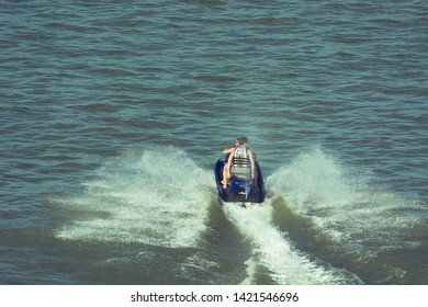 Two guys ride on jet ski on river. Waves from water jet scooter on water surface. Water recreation in province. Russia, Altai region, Barnaul city, Ob river, 12 July, 2014.