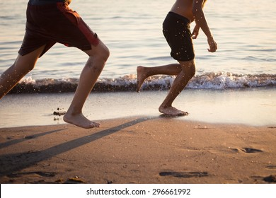 Two guys running on the beach at sunset playing football