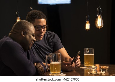 Two guys sharing a cell phone at a bar