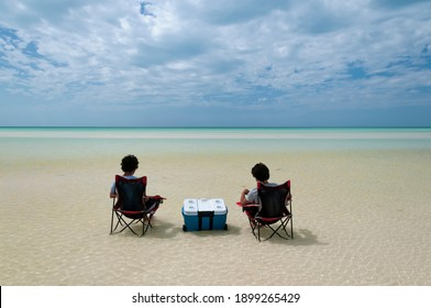 Two guys sitting in the middle of the Caribbean Ocean on chairs and iceboxes, watching the horizon. Holbox Island, Mexico. An ideal place to relax
