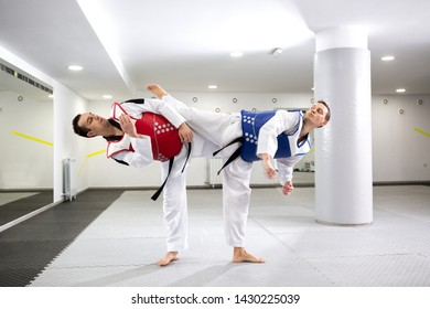 Two guys in a taekwondo combat pushing themselves to their limits