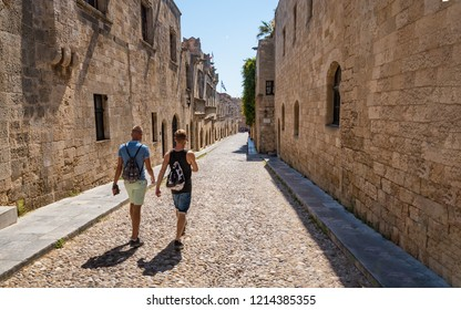 Two guys walking down the street of knights (Ippoton) in City of Rhodes (Rhodes, Greece)