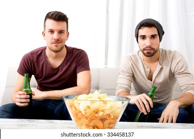 Two guys watching tv, drinking beer, eating crisps at home
