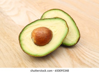 Two half avocado isolated on wooden board