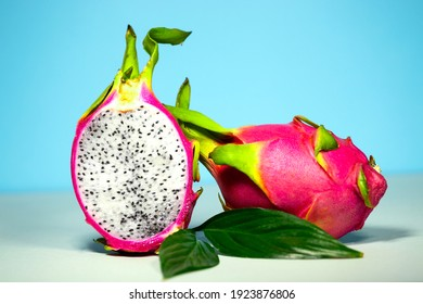 Two Half of Fresh organic Dragon Fruit on a blue background, creative summer food concept, banner background with copy space, Minimalism Trendy Food, Colourful and Delicious Pitahaya