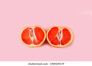 Two half of fresh red cut grapefruit on pink background. Female health concept. Fruit as symbol of vagina. Close up