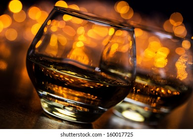 Two half full glasses of cognac on a wooden surface with bright lights behind