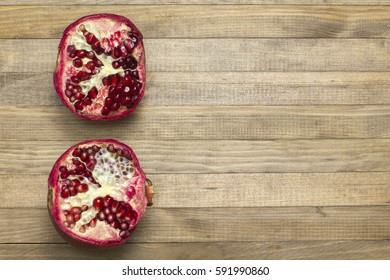 two half pomegranate fruit lay on wooden table