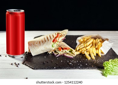 two half sliced shawarma and fri on black slate board next to drink in red aluminum can of 330 ml. Free space for text.