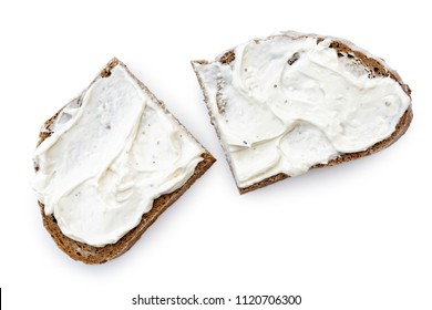 Two half slices of rye bread with cream cheese spread isolated on white from above.