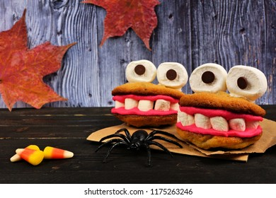 Two Halloween monster cookie treats. Side view scene against a spooky old wood background.
